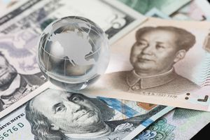 US and China trade barrier, an action by a government that makes trade between the country and other countries more difficult, decoraton glass globe on US dollar and china yuan banknotes
