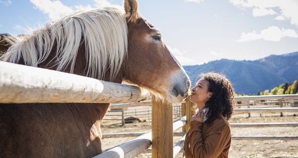 Young woman in western corral with horse