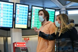 Young couple in face masks at an airport