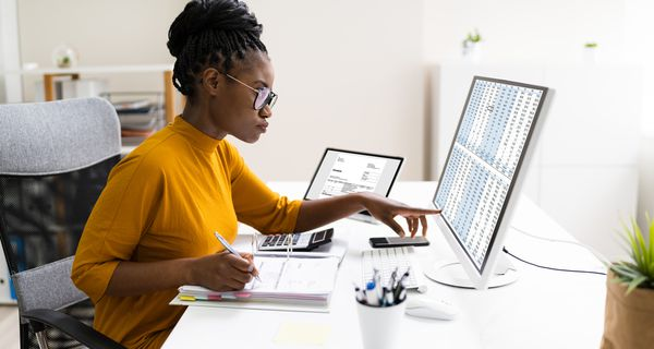 Woman working at desk writing in a binder with a laptop and desktop on her table checking financial information
