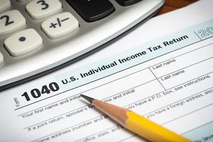 Close-up of a United States tax return form with a pencil and calculator.
