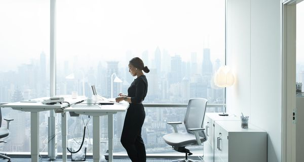 Businesswoman working on computer at a standing desk