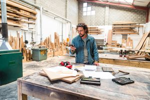 a man in a wood workshop looking at his phone