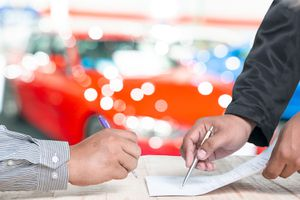 Man Signing Car Insurance Document or Lease Paper