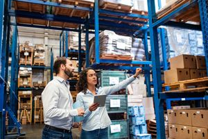 Manager and supervisor taking inventory in warehouse