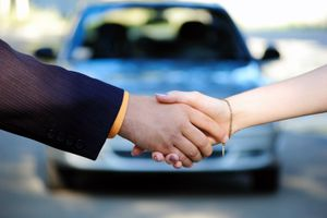 People shaking hands in front of a car after a car sale.