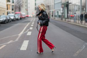 Street style woman in leather jacket and track pants
