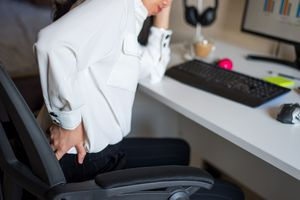 Woman having lower back pain while working from home