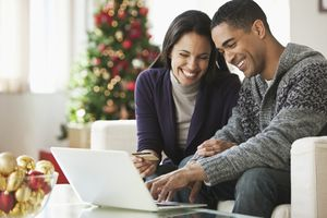 Couple holding credit card and using laptop.