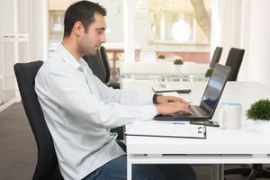 A young man using laptop at the business office.