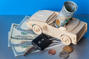 A toy convertible with car keys and hundred dollar bills