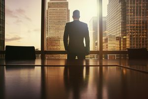Businessman looking out of large office window at skyscrapers at sunset