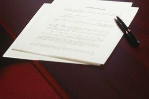 Last Will and Testament on a wood desk with a pen