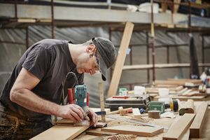 craftsman using electric tools on wood