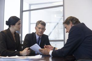 A business meeting with associates analyzing documents.