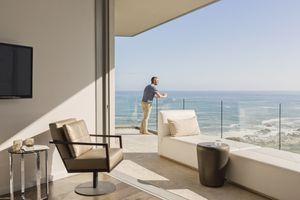 Man enjoying sunny ocean view from luxury balcony.
