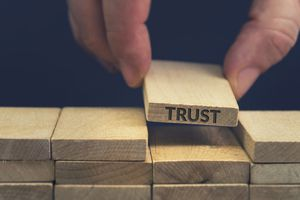 A hand placing a wood block that says trust