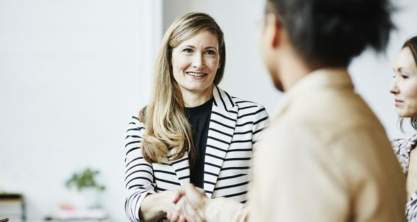Smiling businesswoman shaking hands with client before meeting