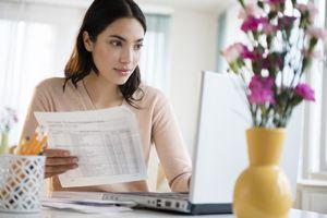 A woman paying bills on laptop.