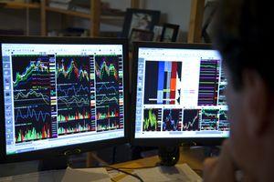 Stock market trader looks at stock charts on monitors