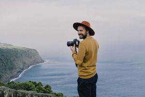 Smiling man with a camera at the coast on Sao Miguel Island, Azores, Portugal