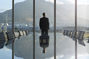 male in a suit in an office with a long table looking out of a big window with a mountain in the background