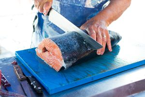 Midsection Of Man Cutting Fish