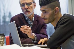 Professor and college student at laptop.