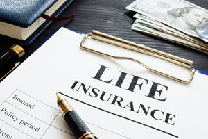 Whole life insurance paperwork, pen, and dollar banknotes.