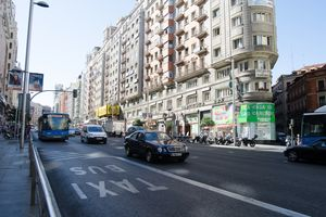 A main street in Madrid, Spain. Full of cars, people. and businesses.