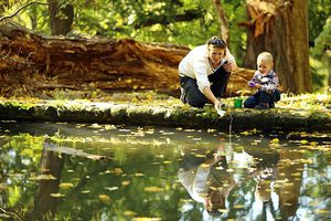 A woman, presumably a mother, teaches her child how to fish in a small forest lake.