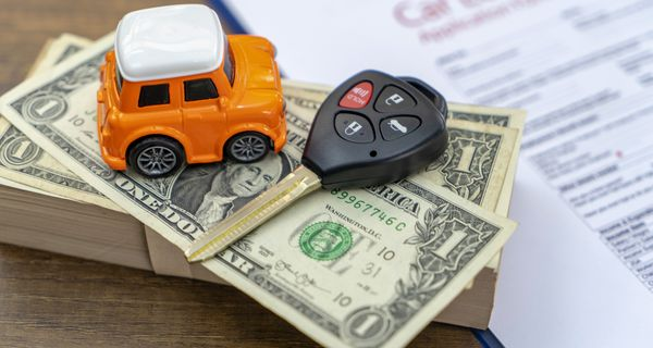 Stack of money with car keys and a toy keychain next to car loan paperwork