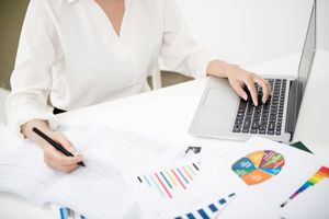 Businesswoman Analyzing Investment Charts With Laptop