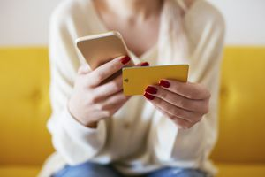 woman using smartphone and using bank card at home