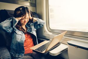 Asian college girl frustrated with laptop on the train.