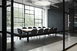 an empty modern conference room with chairs, tables, and a chalkboard wall, in front of an industrial window