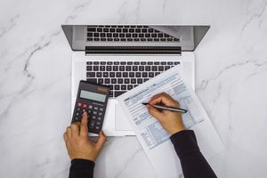 overhead view of a person's hands using a calculator and filling out a tax form on a laptop