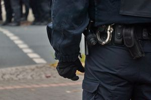 Back of police officer showing handcuffs and gun
