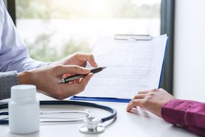 A midsection of doctor showing insurance form to patient.