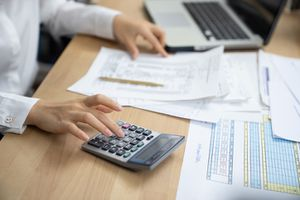woman planning home budget and using calculator