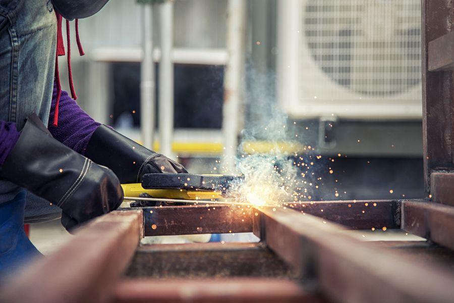 construction worker welding steel concrete form work in construction site