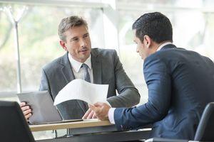 Businessmen negotiating in meeting.