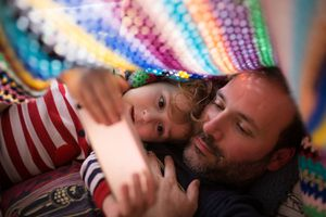 Boy and dad watching something in a smartphone under a colorful blanket