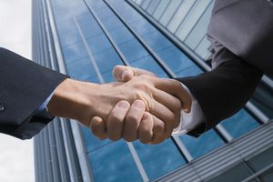 Two businesspeople shaking hands in front of shared real estate property.