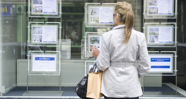 Woman looking at ads in a real estate office window