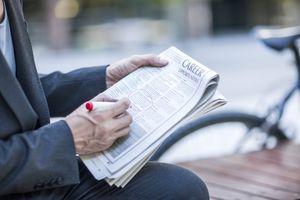 Businessman circling job vacancies in newspaper