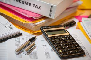 Desk with income tax book, calculator, pen, calendar, etc.