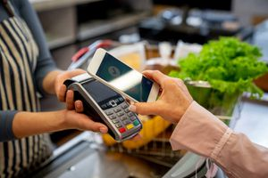 Unrecognizable Female Customer Paying for Groceries With Smartphone