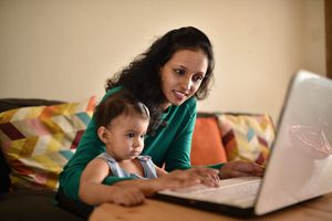 Woman shopping online with her toddler baby in the lap.