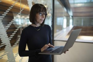 Businesswoman using laptop in office.